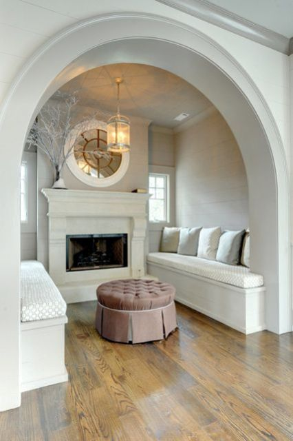 a neutral vintage conversation space with a built-in fireplace, built-in benches and pillows plus a round mirror and branches
