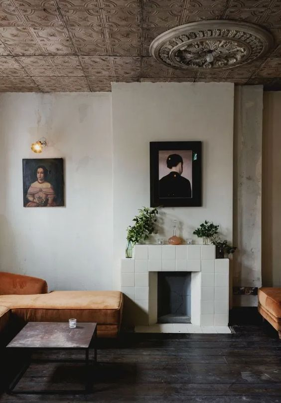 a quirky nook wiht a tiled fireplace, a rust-colored lounger, some artworks and potted plants is a lovely space