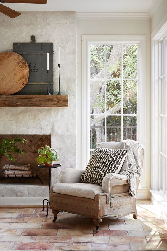 a refined farmhouse nook with a stone clad fireplace, a wooden mantel and a refined chair with a blanket and a pillow is cool