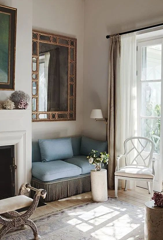 a refined nook with a white fireplace, a whimsy stool, a built-in blue sofa and a large mirror over it