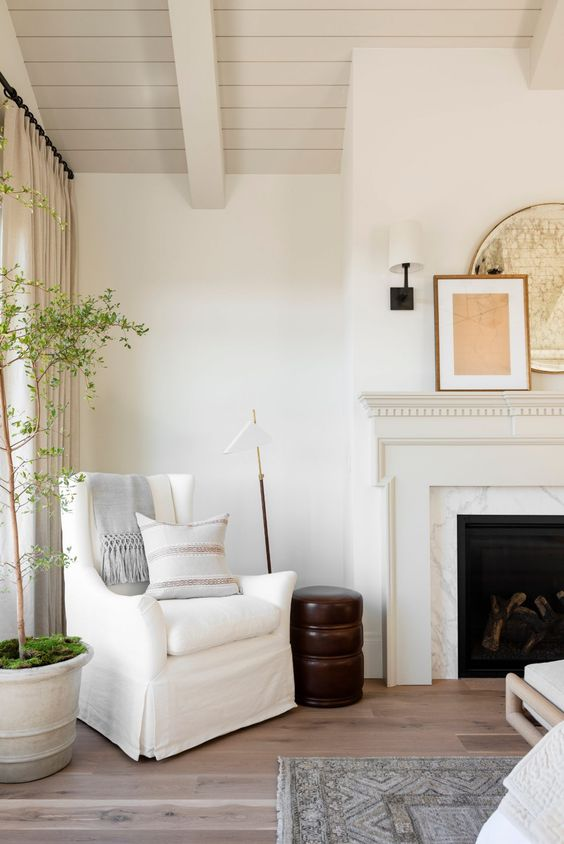 a refined space with a marble clad fireplace, a neutral wooden mantel, a white chair with a pillow and a wooden side table