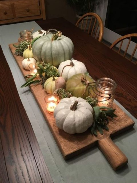 a rustic Thanksgiving centerpiece of a cutting board with heirloom pumpkins, greenery, candles
