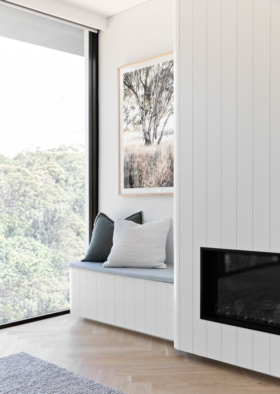 a serene nook with a wood clad built-in fireplace, a built-in bench with pillows and a lovely view plus a chic artwork