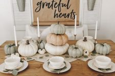 a simple and modern Thanksgiving table with white porcelain, neutral pumpkins stacked and some greenery on the table
