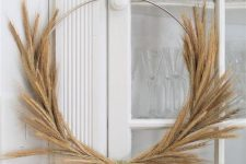 a simple and modern Thanksgiving wreath made of a metal frame and some wheat is a stylish idea for decor