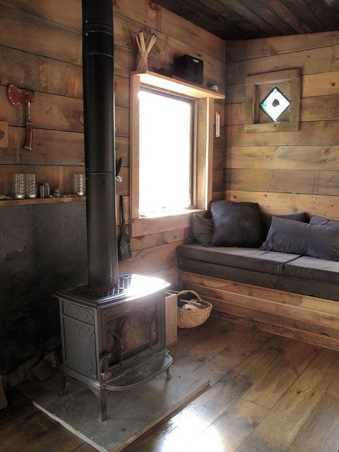 a simple cabin space with a vintage hearth and a wooden bench with cushions and pillows plus shelves and baskets is welcoming