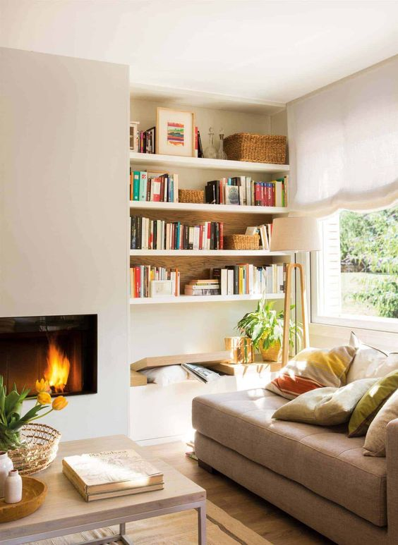 a sleek built-in fireplace, a bench and built-in shelves, a tan couhc with pillows form a cozy and welcoming reading nook