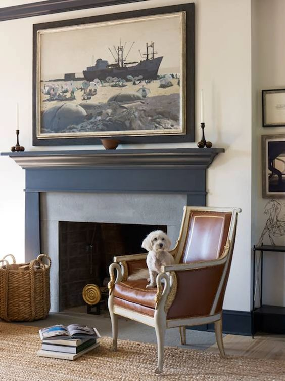 a sophisticated nook with a brick fireplace, a vintage chair and a statement artwork over the fire