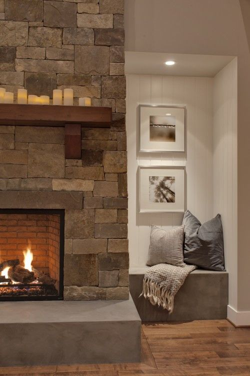 a stone clad fireplace with a concrete sill plate and a built-in concrete seat with pillows for warming up