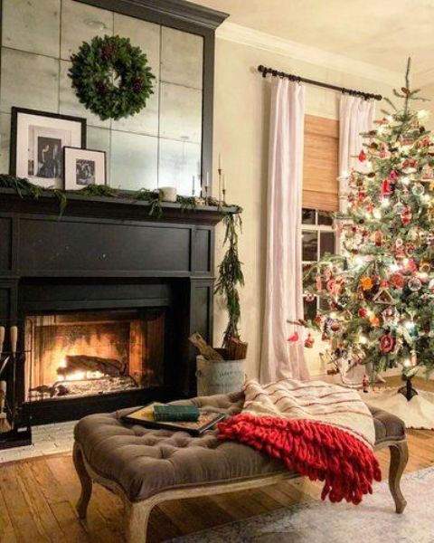 a stylish and welcoming fireplace nook with a black fireplace, a mirror over it, a vintage ottoman and a blanket plus a greenery wreath