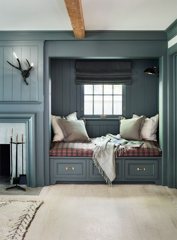 a stylish farmhouse space with a stone clad fireplace, a built-in bench with drawers, a plaid cushion and neutral pillows