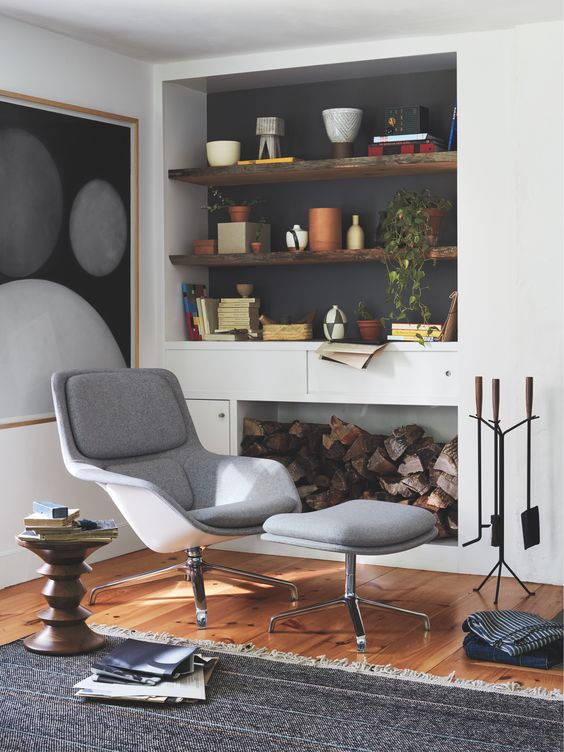 a stylish nook by the fire, with built-in shelves in a niche, a grey lounger with a footrest, some potted greenery