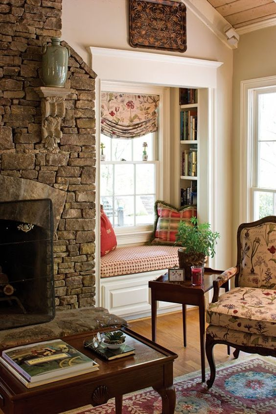 a vintage rustic space with a stone clad fireplace, a small built-in nook with built-in bookshelves and pillows and a floral chair with a table