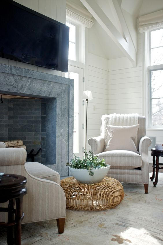 a welcoming farmhouse nook with a brick and stone clad fireplace, tan striped chairs, a rattan coffee table and a potted plant
