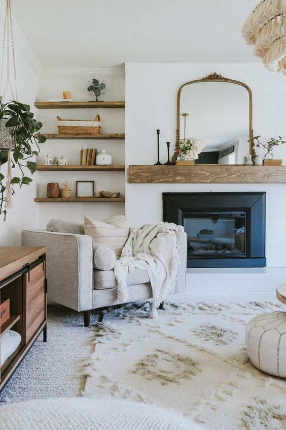 a welcoming farmhouse nook with a built-in fireplace and a wooden mantel, a neutral chair with pillows and built-in shelves