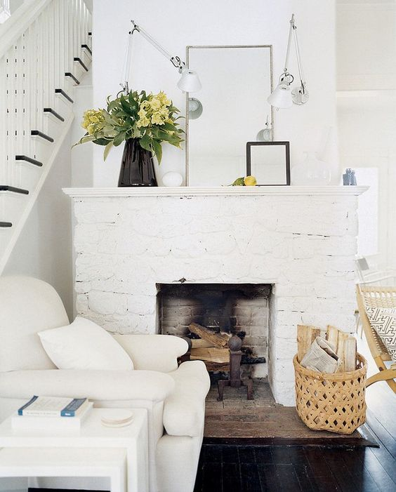 a welcoming farmhouse nook with a white brick clad fireplace, a creamy chair and tables plus a basket for storage