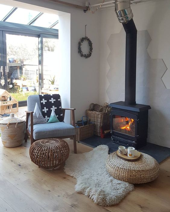 a welcoming modern space with a black hearth, a chair, a rattan table and a jute ottoman and some baskets for firewood