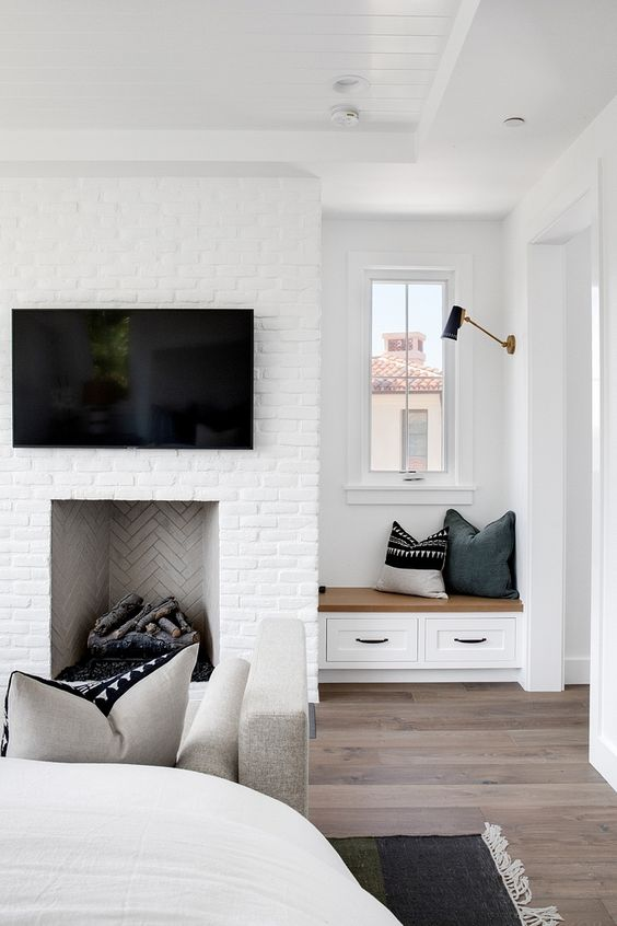 a white brick fireplace with firewood inside and a small built-in windowsill with drawers plus pillows is a welcoming nook
