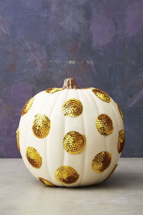 a white pumpkin with large gold sequin polka dots will give a cool glam feel to your Thanksgiving decor