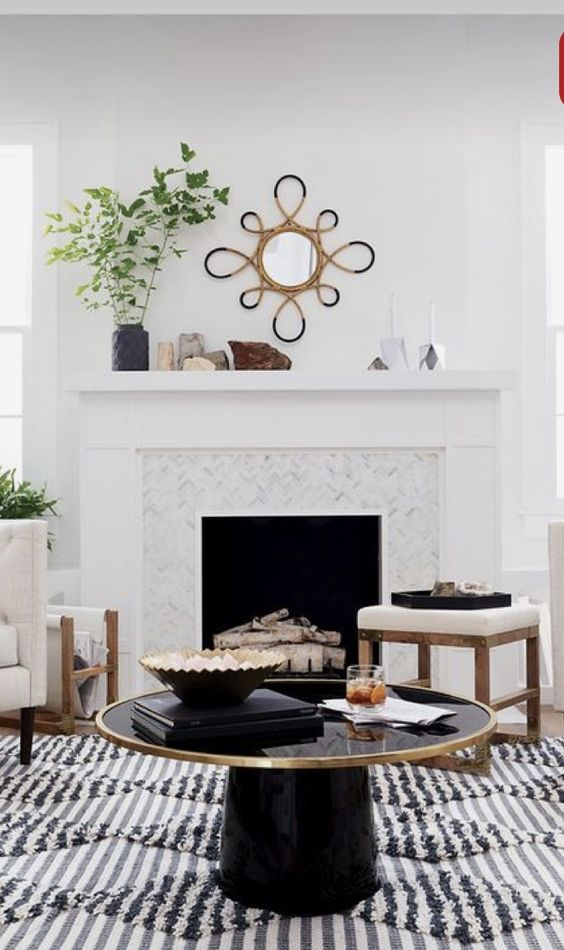 a white tile clad fireplace with firewood, a couple of stools, a mantel with greenery and rocks and a black round table