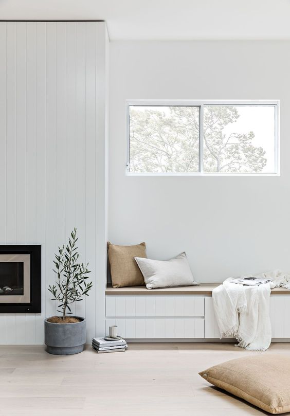 an airy nook with a built in fireplace and a bench with drawers for storage plus pillows and a fringe blanket and a pitted plant