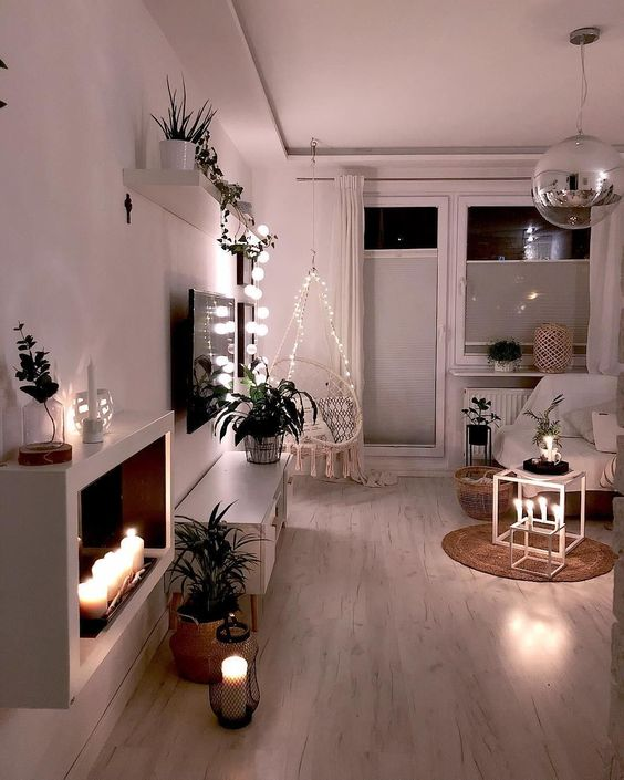 candles in candleholders and lanterns, lights over the chair and on the shelf make the space lit up and cozy