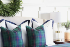 dark plaid bedding and a greenery wreath will easily transform your bedroom into a wintry space