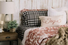 faux fur blankets, plaid bedding, a wooden wreath and potted greenery make the bedroom winter-like and cozy