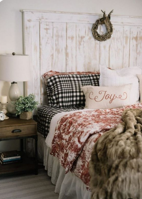 faux fur blankets, plaid bedding, a wooden wreath and potted greenery make the bedroom winter like and cozy