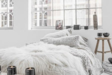 faux fur, candles, bowls and a rough wooden bench plus a knit pillow are ideal for a winter-like Scandinavian bedroom