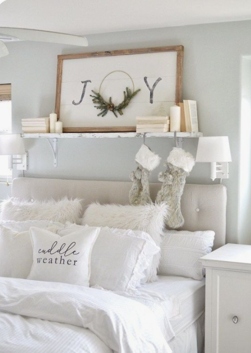 faux fur stockings and pillows, a Christmas sign and some pillar candles make the white bedroom super cozy and chic
