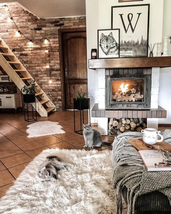layered blankets and fur rugs make the living room very cozy, and the fireplace adds to the ambience