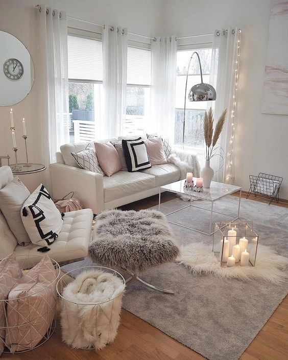 layered fur rugs, a fur stool and a fur blanket make the living room more welcoming and cozy