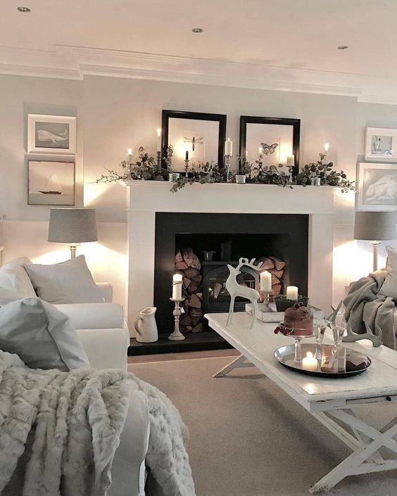 lots of candles and lights and a non-working hearth with firewood make the living room more welcoming