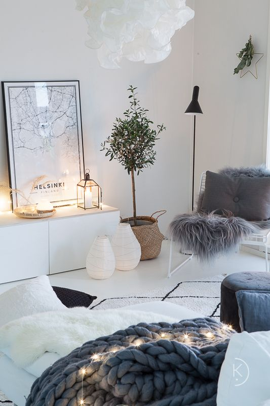 lots of fairy lights here and there and candle lanterns make this Scandinavian living room very cozy