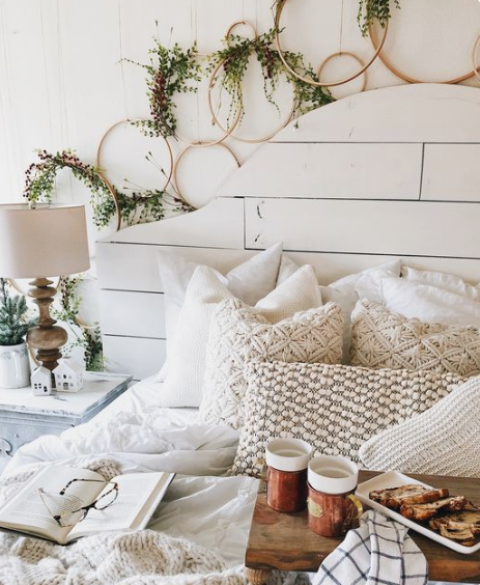 lots of hoop wreaths with greenery, knit and crochet pillows and blankets give the bedroom a cool and cozy winter look