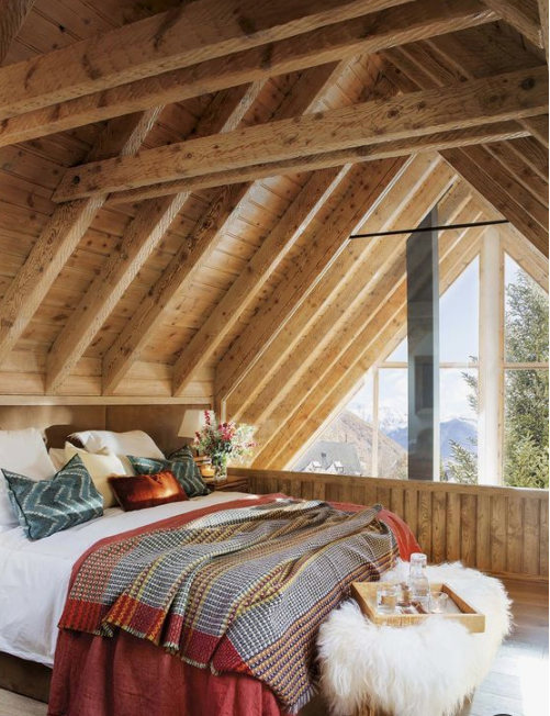 plaid and knit bedding and pillows, a faux fur ottoman make this cabin bedroom very chic and welcoming