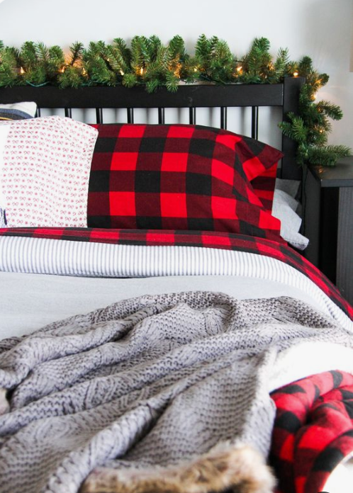 plaid and knit bedding, evergreens with lights bring astrong holiday feel to the bedroom