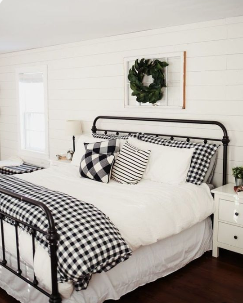 plaid bedding and a fresh greenery wreath over the bed make the bedroom clasically Christmassy