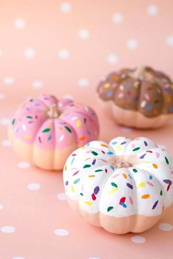 pumpkins painted as pretty donuts are a creative and delicious Thanksgiving decoration to try