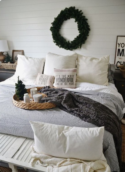 white and chocolate brown knit blankets, printed pillows, an evergreen wreath and a mini Christmas tree for a winter fele in the space