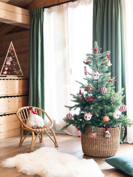a Christmas tree in a basket with colorful and pretty ornaments is a lovely decoration for the holidays and it will look amazing always