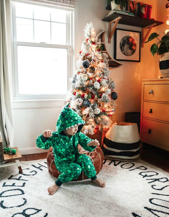 a flocked Christmas tree decorated with lights and pompom ornaments is a beautiful decoration you can provide for your kids