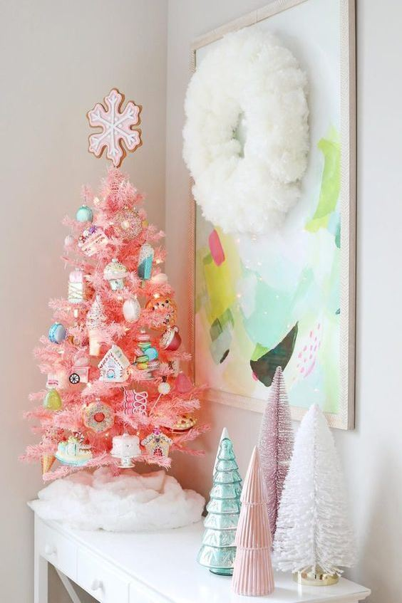 a hot pink Christmas tree with fun and whimsical ornaments and a cookie tree topper for creating a holiday feel in the space