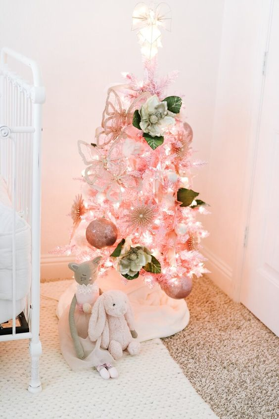 a lovely pink Christmas tree with lights, fabric blooms and pink ornaments is amazing for a little princess nursery at Christmas