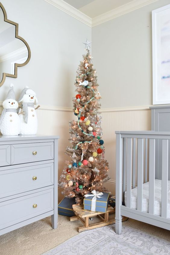 a metallic Christmas tree with lights, pretty ornaments and colorful pompom garlands is a lovely idea for any kids' room