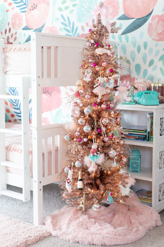 a shiny metallic Christmas tree with bright ornaments and a pink faux fur tree skirt will add a holiday feel to the space