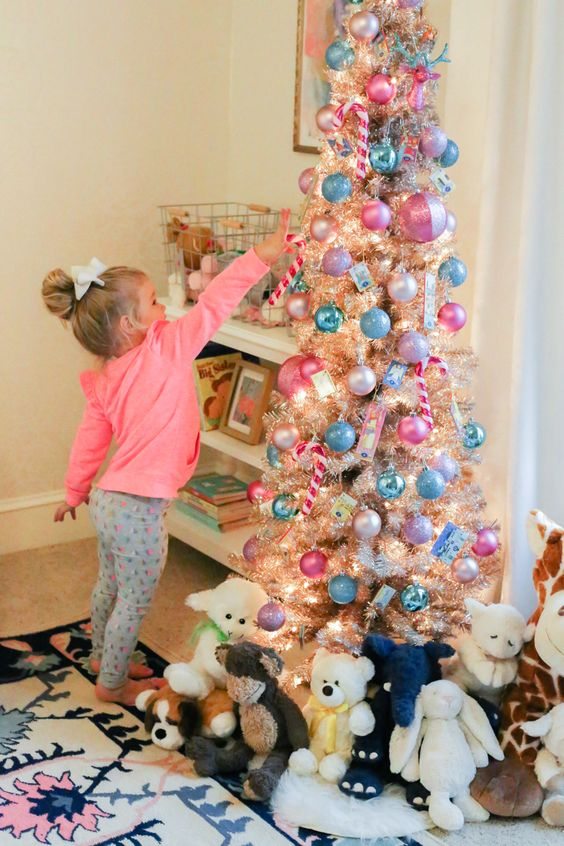 a shiny metallic Christmas tree with pink and blue ornaments, lights and toys under the tree is a lovely and bold idea
