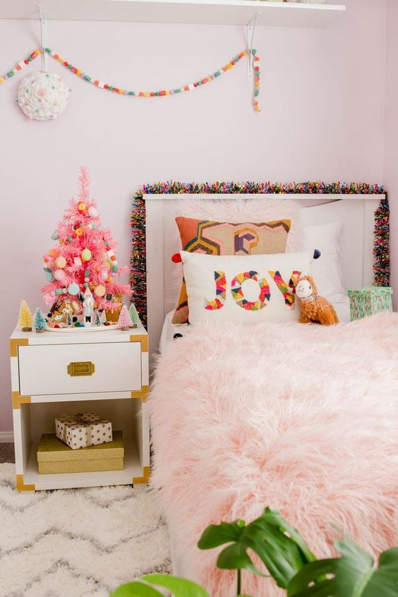 a tiny pink Christmas tree with colorful ornaments, a bright pompom garland and a printed pillow for holiday