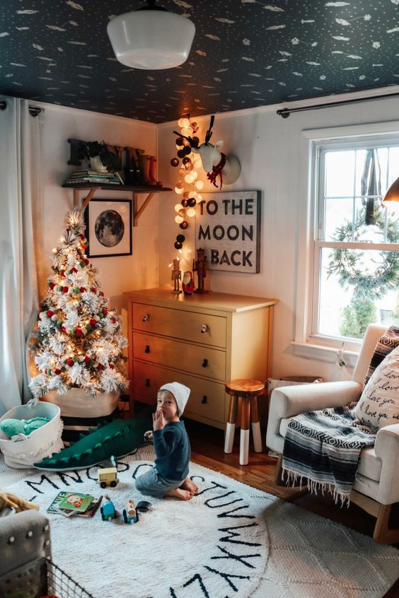 a white Christmas tree with lights and red and green ornaments, a deer head with lights will bring a strong festive feel to the space